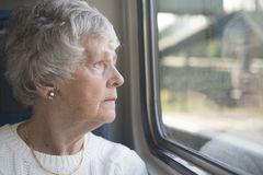 One senior woman looking out of the window Stock Photo