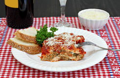 One serving of eggplant parmesan with sides of wine and parmesan Royalty Free Stock Photos