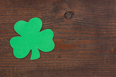 One Shamrock on Wood. A green shamrock on aged weather beaten brown knotted wood royalty free stock photography