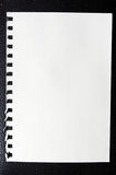 One sheet from notebook. On black leather Royalty Free Stock Photos