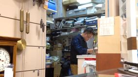 One side of clock and watch store with worker fixing watch stock footage