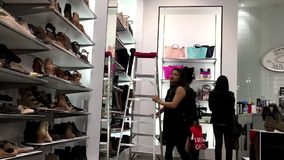 One side of people buying new shoes. Inside Steve madden shoes store stock video footage