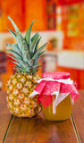 On one side a pineapple on the other a delicious jam made of these fruit on a wooden table,. Promoting Royalty Free Stock Photography