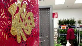 One side of selling Chinese New Year scroll display and shopper walking through. Inside Walmart store