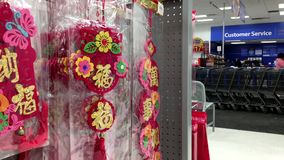 One side of selling Chinese New Year scroll display and shopper walking through service counter. Inside Walmart store