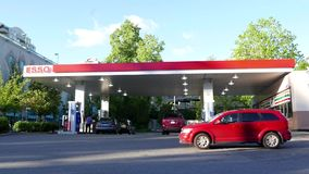One side of several cars filling fuel at Esso gas station. In New Westminster stock footage