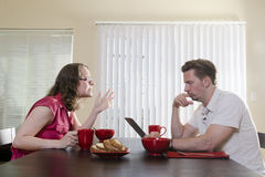 One-sided conversation. A frustrated wife becomes angry with her husband at the breakfast table as he ignores her while reading his tablet Royalty Free Stock Photo
