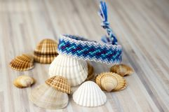One simple blue handmade homemade natural woven bracelets of friendship on white wooden table and sea shells Royalty Free Stock Images