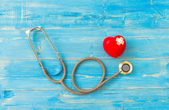 One single alone red heart love shape hand exercise ball with bandage MD medical doctor physician`s stethoscope blue wood backgro Royalty Free Stock Photo