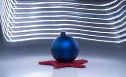 One single blue christmas tree ball on a dark grey background light effects. Blue christmas tree ball on a dark grey background with light effects Royalty Free Stock Image