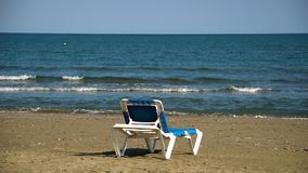 One chaise-longue at perfect wild sandy beach with blue sea view, nobody, travel destinations concept stock footage