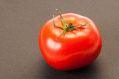 One single perfect red tomato on dark table or background Stock Photos