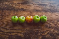 One single red apple among other green ones on wooden table. Concept of choosing the best produce royalty free stock image