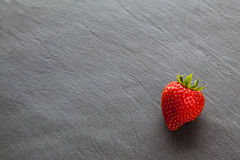 One single ripe red strawberry, with text / copy space. Royalty Free Stock Images