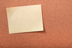 One single yellow oblong sticky post note cork background Royalty Free Stock Photo