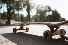 Skateboard on the road. Extreme sport challenge. One skateboard on the road. Extreme sport challenge and skateboarder competition, close up picture of skate Royalty Free Stock Photo