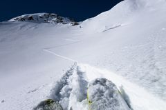 Skiers laying down switchback touring tracks to mountain pass Stock Image
