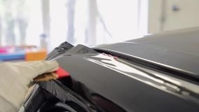 One skilled in the body shop applies vinyl surface to the middle of the vehicle. stock video