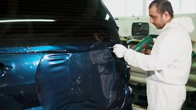 One skilled in the body shop applies vinyl surface to the vehicle. stock video
