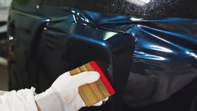 One skilled in the body shop applies vinyl surface to the vehicle. stock video footage