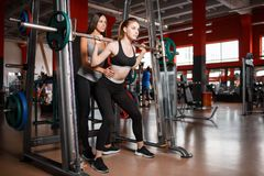 One girl crouches down with a barbell and the second she insures. Royalty Free Stock Image