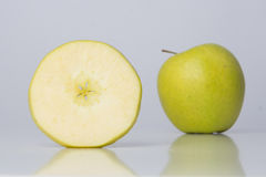 One slice of apple and one whole apple. One slice of green healthy apple and one whole apple Royalty Free Stock Photo