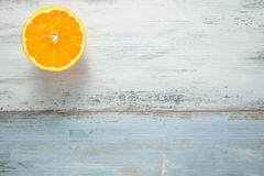 One slice of fresh oranges on painted wooden board Royalty Free Stock Photography