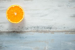 One slice of fresh oranges on painted wooden board Stock Image