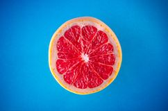 One slice of grapefruit on a blue background, horizontal shot. Picture presents One slice of grapefruit on a blue background, horizontal shot Royalty Free Stock Photos