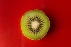 One slice of kiwi fruit  on red background, horizontal shot Royalty Free Stock Image