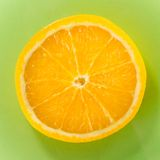 One slice of orange closeup on green background, square shot Stock Photography