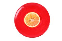 One slice of orange on a red plate Royalty Free Stock Photography
