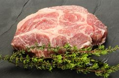 Slice raw pork neck with thyme on slate Royalty Free Stock Image