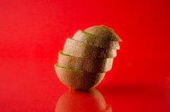 One sliced kiwi fruit  on red background, horizontal shot. Picture presents one sliced kiwi fruit  on red background, horizontal shot Royalty Free Stock Photo