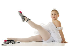 One Slipper Tied. A seated elemantary-aged ballerina in her dance costume, gracefully lifting a leg with her zebra-stripped slippers.  On a white background Stock Image