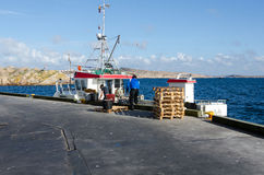 One small fishingboat unload their cargo. With Stock Image
