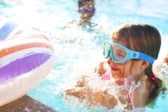 One small girl having fun in outdoor pool Royalty Free Stock Images