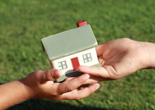 One small kids hand giving a model of a house. To another small kids hand stock photos