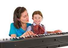 One small little boy playing piano. One small little boy learning to play piano with the teacher. Isolated objects Royalty Free Stock Photo