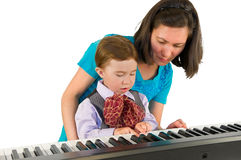 One small little boy playing piano. One small little boy learning to play piano with the teacher. Isolated objects Royalty Free Stock Photos