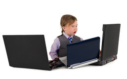 One small little boy working on laptops. One small little boy wearing pink shirt, necktie, suit is working on three laptops. Business concept. Isolated objects Stock Photography