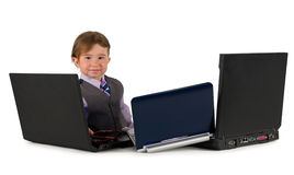 One small little boy working on laptops. One small little boy wearing pink shirt, necktie, suit is working on three laptops. Business concept. Isolated objects Royalty Free Stock Photos