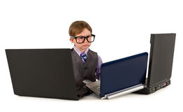 One small little boy working on laptops. One small little boy wearing pink shirt, necktie, suit is working on three laptops. Business concept. Isolated objects Stock Images