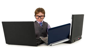 One small little boy working on laptops. One small little boy wearing pink shirt, necktie, suit is working on three laptops. Business concept. Isolated objects Royalty Free Stock Image
