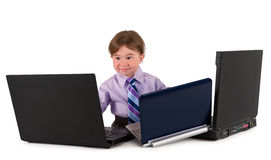 One small little boy working on laptops. One small little boy wearing pink shirt, necktie, suit is working on three laptops. Business concept. Isolated objects Royalty Free Stock Images