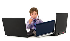 One small little boy working on laptops. One small little boy wearing pink shirt, necktie, suit is working on three laptops. Business concept. Isolated objects Royalty Free Stock Photography