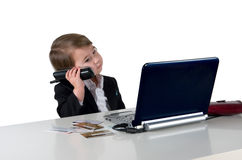 One small little girl (boy) calling phone. Wearing black suit, computer, credit cards and phone on table. Business concept. Isolated object Stock Photos