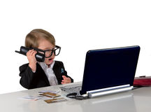 One small little girl (boy) with glasses, computer and credit ca. One small little girl (boy) calling phone, wearing black suit and glasses. Computer, credit Stock Photos