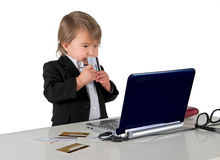 One small little girl (boy) holding credit card. Wearing black suit. Computer, credit cards, glasses and phone are on table. Business concept. Isolated object Royalty Free Stock Photos