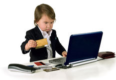 One small little girl (boy) with phone, computer and credit card. One small little girl (boy) wearing black suit. Computer, credit cards and phone are on table Stock Photo